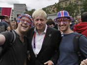 London Mayor Boris Johnson, poses for pictures with Britain team fans, following a photo-op with London ambassadors, the volunteers working around the city to give tourists directions and information, in central London.