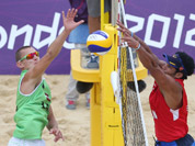 Martins Plavins, from Latvia spikes a ball past Igor Hernandez, from Venezuela during their Beach Volleyball match at the 2012 Summer Olympics in London.