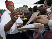Serena Williams of the United States signs autographs after a doubles match at the All England Lawn Tennis Club in Wimbledon, London at the 2012 Summer Olympics.