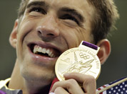 United States` Michael Phelps poses with his gold medal for the men`s 4x200-meter freestyle relay swimming final at the Aquatics Centre in the Olympic Park during the 2012 Summer Olympics in London.