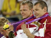 Latvia`s Janis Smedins, left, and Martins Plavins celebrate with their bronze medals during medal ceremonies at the Beach Volleyball Venue at the 2012 Summer Olympics.