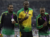 Jamaica`s gold medal winner Usain Bolt is flanked by his teammates silver medal winner Yohan Blake, left, and bronze medalist Warren Weir during the ceremony for the men`s 200-meter final during the athletics in the Olympic.