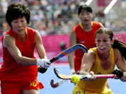 China`s Gao Lihua (10) and Australia`s Jayde Taylor (21) vie for the ball during their women`s field hockey classification match at the 2012 Summer Olympics in London.