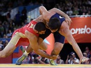 Bilyal Makhov of Russia competes against Jamaladdin Magomedov of Azerbaijan (in blue) during the men`s 120-kg freestyle wrestling competition at the 2012 Summer Olympics.
