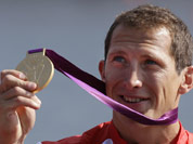 Great Britain`s Ed McKeever displays the gold medal he won in the men`s kayak single 200m in Eton Dorney, near Windsor, England, at the 2012 Summer Olympics.