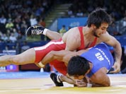 Ramazan Sahin of Turkey competes with Ikhtiyor Navruzov of Uzbekistan (in blue) during their 66-kg freestyle wrestling match at the 2012 Summer Olympics.
