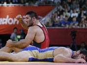 Reza Mohammad Ali Yazdani of Iran, (in red) and Abdusalam Gadisov of Russia, (in blue) finish their 96-kg freestyle wrestling match at the 2012 Summer Olympics.