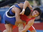 Ikhtiyor Navruzov, competes with Sushil Kumar of India, (in blue) during their 66-kg freestyle wrestling match at the 2012 Summer Olympics.