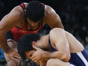Ikhtiyor Navruzov of Uzbekistan, competes with Sushil Kumar, (in blue) during their 66-kg freestyle wrestling match at the 2012 Summer Olympics.