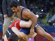 Akzhurek Tanatarov of Kazakhstan, competes with Sushil Kumar of India, (in blue) during their 66-kg freestyle wrestling match at the 2012 Summer Olympics.