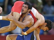 Ikhtiyor Navruzov of Uzbekistan, competes with Sushil Kumar of India, (in blue) during their 66-kg freestyle wrestling match at the 2012 Summer Olympics.