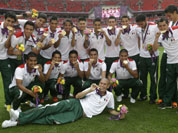 Mexican players pose for photos with their gold medals after winning the men`s soccer final against Brazil at the 2012 Summer Olympics in London