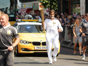 In this photo provided by LOCOG, Amitabh Bachchan carries the Olympic flame on the torch relay leg between The City of London and the borough of Southwark in London.