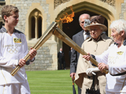 This image made available by LOCOG shows Queen Elizabeth II, second right, and the Duke of Edinburgh watching the Torch Kiss as Torchbearer 073 Gina Macgregor, right, passes the Olympic Flame to Torchbearer 074 Phillip Wells, left, outside Windsor Castle, Windsor, England