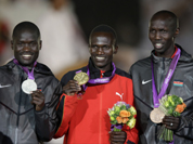 Men`s marathon gold medalist Uganda`s Stephen Kiprotich, center, is flanked by silver medalist Abel Kirui, of Kenya, left, and bronze medalist Wilson Kipsang Kiprotich, at the 2012 Summer Olympics, Sunday, Aug. 12, 2012, in London. 