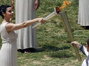 A high priestess, holding a lit torch and an olive branch, performs during the final dress rehearsal for the lighting of the Olympic flame held in Ancient Olympia, Greece