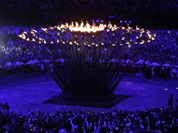 Will.i.am of the Black Eyed Peas passes the Olympic Flame to torchbearer Emma Fowler in Taunton, England