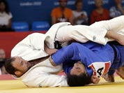 Jevgenijs Borodavko of Latvia competes against Anthony Liu of American Samoa (in blue) during the men`s 100-kg judo competition at the 2012 Summer Olympics.