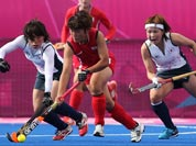 South Korea`s Park Mi-Hyun and Japan`s Yukari Yamamoto, vie for the ball as Japan`s Nagisa Hayashi, looks on in the women`s hockey preliminary round match at the 2012 Summer Olympics.