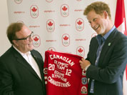 Prince Harry receives a Canadian team jacket from Canadian Olympic Committee President Marcel Aubut during his visit to Canada House at the 2012 Summer Olympics.