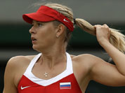 Maria Sharapova of Russia pulls her ponytail as she plays against Sabine Lisicki of Germany at the All England Lawn Tennis Club at Wimbledon, in London, at the 2012 Summer Olympics.