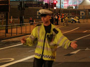 A police officer stands at the scene where the driver of an official Olympic bus carrying journalists has been arrested after a bicyclist was hit and killed, near the Olympic Park in Stratford, London.