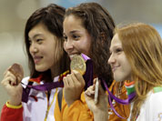 China`s Tang Yi, Netherlands` Ranomi Kromowidjojo and Belarus` Aliaksandra Herasimenia pose with their medals for the women`s 100-meter freestyle swimming final at the Aquatics Centre in the Olympic Park during the 2012 Summer Olympics in London.