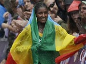 Ethiopia`s gold medal winner Tiki Gelana celebrates with her country`s flag after the women`s marathon at the 2012 Summer Olympics.