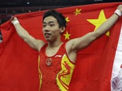 Chinese gymnast Zou Kai holds his national flag after winning the gold for the men`s floor exercise finals at the 2012 Summer Olympics.