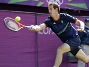 Andy Murray of Great Britain returns to Roger Federer of Switzerland during the gold medal men`s singles match at the All England Lawn Tennis Club in Wimbledon, London at the 2012 Summer Olympics.