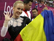 Romania`s gymnast Sandra Raluca Izbasa holds her national flag and celebrates after winning the gold medal for the artistic gymnastics women`s vault finals at the 2012 Summer Olympics.