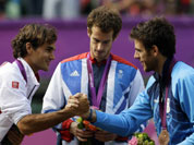 Silver medalist Switzerland`s Roger Federer, right, shakes hands with bronze medalist Juan Martin del Potro of Argentina, right, as Gold medalist Andy Murray of Great Britain, center, stands during the medal ceremony of the men`s singles event at the All England Lawn Tennis Club at Wimbledon in London Olympics