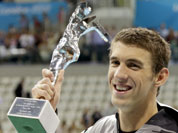 United States` swimmer Michael Phelps holds up a silver trophy after being honored as the most decorated Olympian at the Aquatics Centre in the Olympic Park during the 2012 Summer Olympics in London