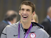 United States` swimmer Michael Phelps smiles as he wears his gold medal at the Aquatics Centre in the Olympic Park during the 2012 Summer Olympics.