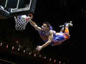 An ariel performer flies and slams a dunk during halftime of a women`s basketball game between Russia and France at the 2012 Summer Olympics.