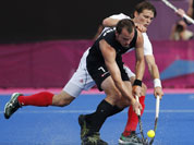 Belgium`s Felix Denayer and New Zealand`s Blair Hopping, front, battle for the ball in the men`s hockey preliminary round match at the 2012 Summer Olympics.