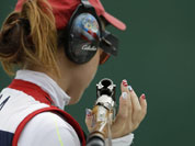 United States of America`s Corey Cogdell holds her gun, with fingernails painted in designs in the colors of the U.S. flag, as she waits her turn to shoot, during qualifiers for the women`s trap event, at the 2012 Summer Olympics.