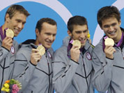United States` men`s 4 X 100-meter medley relay team from left, Matthew Grevers, Brendan Hansen, Michael Phelps and Nathan Adrian hold their gold medals at the Aquatics Centre in the Olympic Park during the 2012 Summer Olympics in London