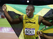 Usain Bolt, left, holds his national flag as teammate Yohan Blake, right, poses with him after Bolt`s win in the men`s 100-meter final during the athletics in the Olympic Stadium at the 2012 Summer Olympics.