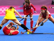 China`s Fu Baorong, left, Japan`s Keiko Manabe , left on ground, and Nagisa Hayashi vie for the ball in the preliminary round women`s hockey match at the 2012 Summer Olympics.
