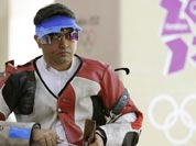 Gagan Narang adjusts his rifle as he prepares to switch from prone to standing position, during qualifiers for the men`s 50-meter rifle 3 positions, at the 2012 Summer Olympics.