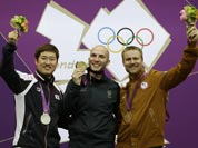 Gold medal winner Italy`s Niccolo Campriani, center, poses for a picture with silver medalist Kim Jonghyun of South Korea, left, and bronze medalist Matthew Emmons of the United States of America, during the victory ceremony for the men`s 50-meter rifle 3 positions event, at the 2012 Summer Olympics