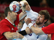 Serbia`s Momir Rnic, right, is tackled by Hungary`s Ferenc Ilyes, left, during their men`s handball preliminary match at the 2012 Summer Olympics in London