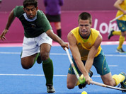 Pakistan`s Muhammad Imran, and Australia`s Matt Gohdes vie for the ball in their preliminary round hockey match at the 2012 Summer Olympics in London.