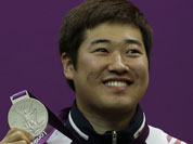 South Korea`s Kim Jonghyun holds up his silver medal, during the victory ceremony for the men`s 50-meter rifle 3 positions event, at the 2012 Summer Olympics.