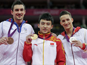 Chinese gold medallist gymnast Feng Zhe, center, Germany`s silver medallist Marcel Nguyen, right, and bronze medallist Hamilton Sabot from France display their medals for the parallel bars during the artistic gymnastics men`s apparatus finals at the 2012 Summer Olympics.