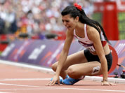 Turkey`s Merve Aydin sits down after the finish line in a women`s 800-meter heat during the athletics in the Olympic Stadium at the 2012 Summer Olympics in London