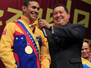 Venezuelan fencer Ruben Limardo, left, holding a replica of a sword once used by South American independence hero Simon Bolivar and Venezuela`s President Hugo Chavez, right, smile during a ceremony in Caracas, Venezuela.