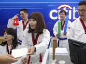 Employees clad in Taekwondo uniform work at a Citibank branch in Seoul. They Wednesday wore the uniforms to show their support for South Koreans competing in Taekwodo at the London Olympics.