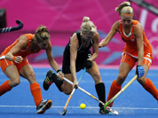 New Zealand`s Emily Naylor contests for the ball with Netherlands Kitty van Male, and Eva de Goede in the women`s hockey semifinal match at the 2012 Summer Olympics in London.